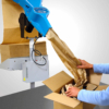 FillPak TT angebracht an einen Packtisch bei der Produktion des Füllpapiers. Dabei wird das Papier direkt in einen Karton ausgegeben.