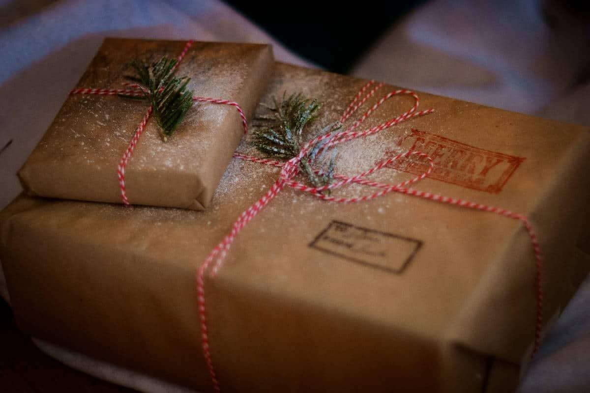 Einfaches Packpapier als Geschenkverpackung. Aufgepeppt mit einer roten Kordel und einen Tannenzweig.